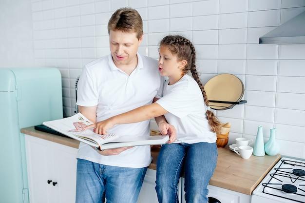 Pai e filha estão assistindo a uma receita em um livro de receitas na cozinha