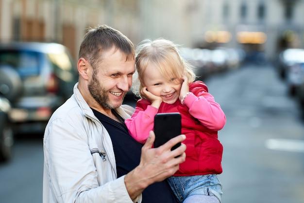 Pai e filha estão assistindo vídeo no telefone ao ar livre