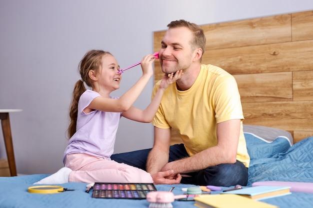 Pai e filha estão brincando em casa, sentados na cama. linda garota engraçada aplicando cosméticos no rosto do pai