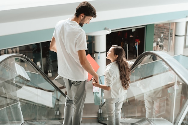 Pai e filha estão descendo a escada rolante.
