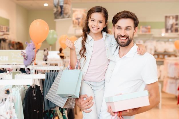 Pai e filha estão na loja de roupas de shopping center.