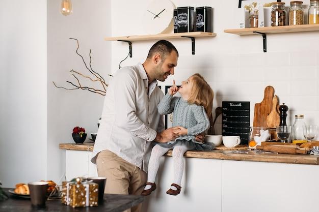 Pai e filha estão se divertindo na cozinha em casa