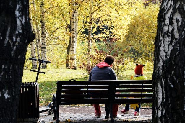 Pai e filha estão sentados em um banco no parque e tomar um lanche de milho