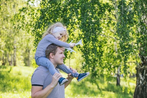 Pai e filha família lindos e felizes juntos no campo jogando aviões