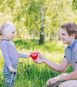 Pai e filha família uma bela e feliz juntos na natureza dá coração vermelho