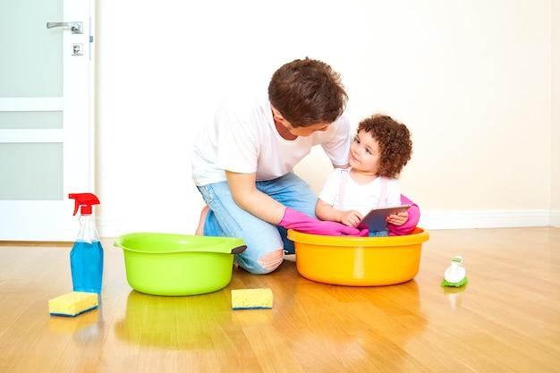 Pai e filha fazem a limpeza e brincam de tablet cuidando de uma família feliz, pais brincam com seus filhos