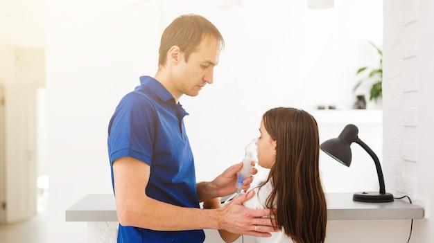 Pai e filha fazem inalações. pai atencioso ajuda a filha a respirar pela máscara. tratamento do trato respiratório.