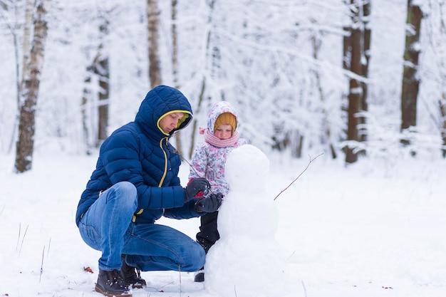 Pai e filha fazem um boneco de neve na floresta de inverno