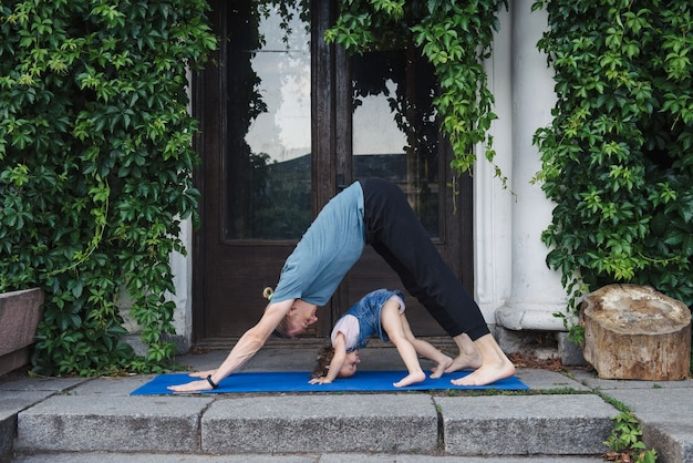 Pai e filha fazendo ioga juntos ao ar livre no parque perto do antigo edifício. família feliz passa tempo junta. conceito de estilo de vida saudável.