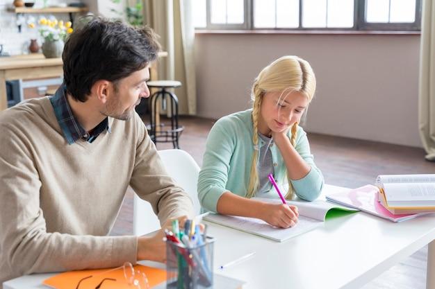 Pai e filha fazendo lição de casa dentro de casa