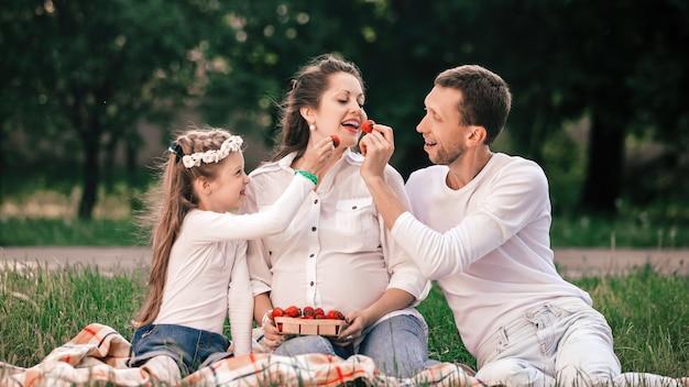 Pai e filha felizes alimentam a mãe com morangos em um piquenique