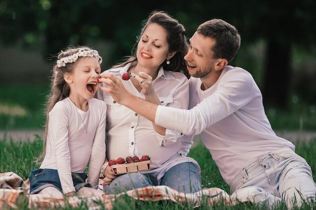 Pai e filha felizes alimentam a mãe com morangos em um piquenique.