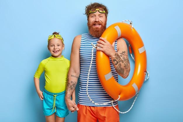 Pai e filha felizes e amigáveis, prontos para nadar, passar férias frescas de verão juntos, usar óculos de proteção, segurar uma bóia salva-vidas laranja, usar camisetas e shorts casuais, dar as mãos, isolado na parede azul