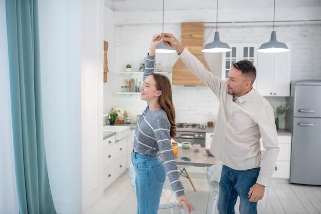 Pai e filha felizes e sorridentes, segurando as mãos um do outro, dançando em casa.