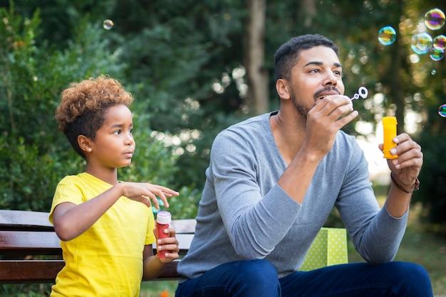 Pai e filha felizes soprando bolhas de sabão