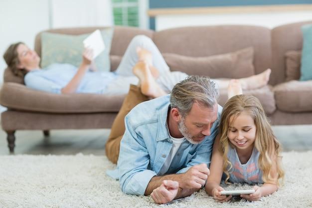 Pai e filha felizes usando um telefone celular enquanto estavam deitados no chão da sala de estar