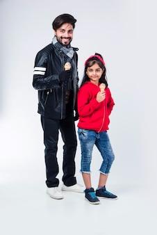 Pai e filha indiano tomando sorvete no cone enquanto usavam roupas quentes em fundo branco