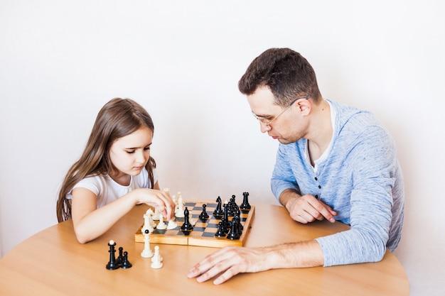 Pai e filha jogam em casa, xadrez, quebra-cabeça para o desenvolvimento do cérebro, inteligência mental