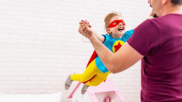 Pai e filha jogam super-herói.
