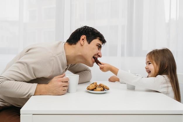 Pai e filha juntos em casa comendo