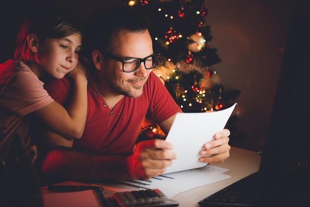 Pai e filha lendo a lista de desejos de natal