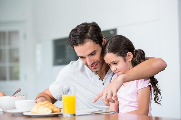 Pai e filha lendo jornal