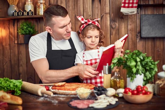 Pai e filha lendo receitas livro enquanto cozinha pizza