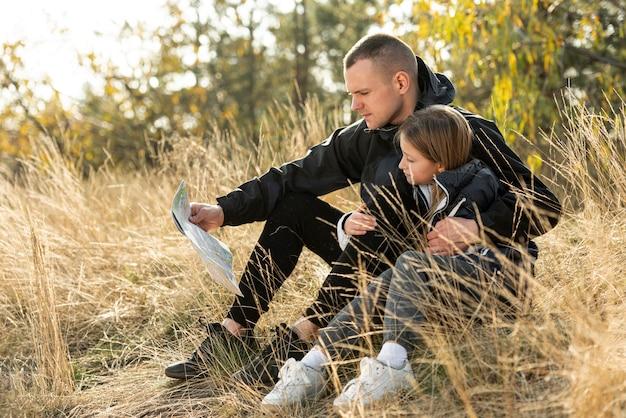 Pai e filha lendo um mapa na natureza