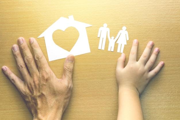 Pai e filha mãos com pequeno modelo de casa e família em fundo de madeira