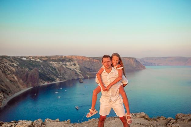 Pai e filha na beira da falésia apreciam a vista no topo da montanha de pedra ao pôr do sol