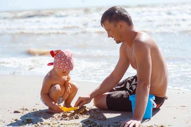 Pai e filha na praia brincando e construindo castelo de areia