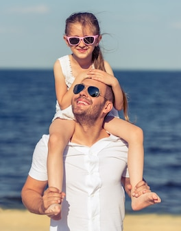 Pai e filha na praia juntos.