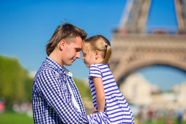 Pai e filha na torre eiffel de paris.