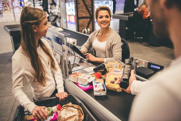 Pai e filha no balcão de caixa no supermercado.
