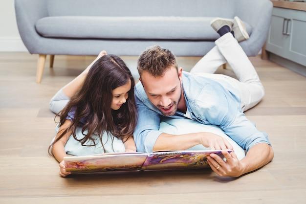 Pai e filha olhando no livro de imagens enquanto estava deitado no chão