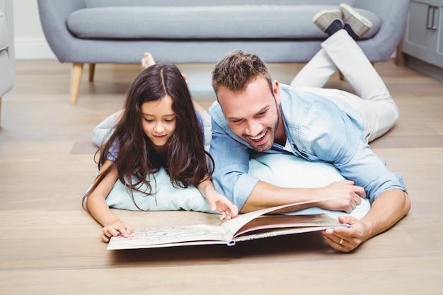 Pai e filha olhando no livro de imagens no chão