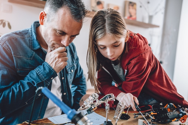 Pai e filha olhando para esquemas eletrônicos