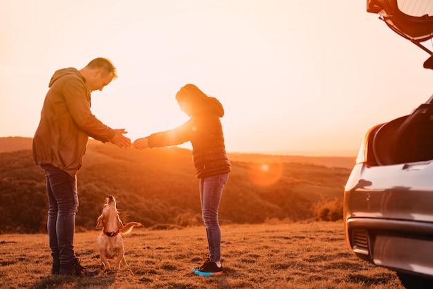 Pai e filha pagando com cachorro no acampamento na colina