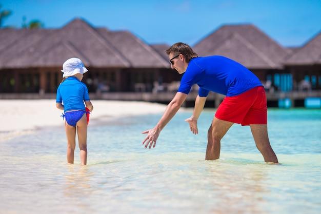 Pai e filha pegando peixe na praia tropical