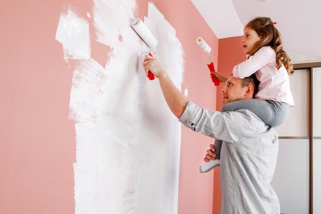 Pai e filha pintam a parede da sala. reforma de casa
