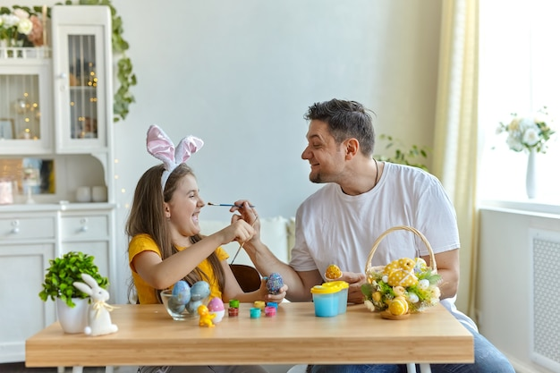 Pai e filha pintam o rosto um do outro com tinta azul para pintar ovos. sobre a mesa está uma cesta com ovos de páscoa e tintas.