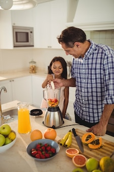 Pai e filha preparando batido na cozinha