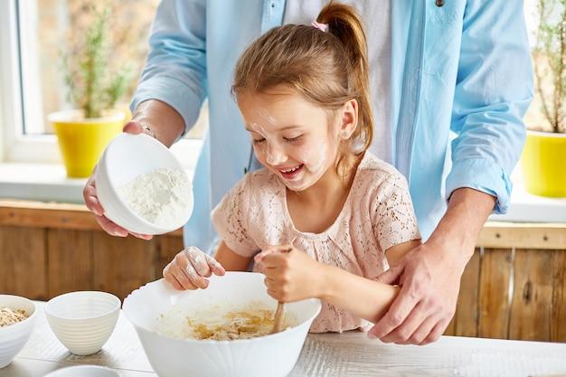 Pai e filha preparando massa juntos na cozinha, adicionando farinha na tigela para cozinhar massa em casa
