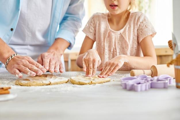 Pai e filha preparando massa juntos na cozinha, família cozinhando em casa, conceito de fim de semana