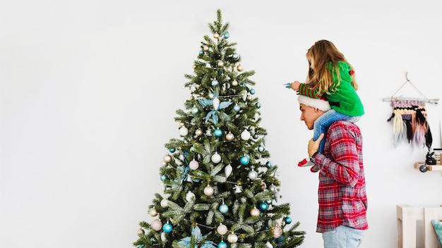 Pai e filha que decoram a árvore de natal