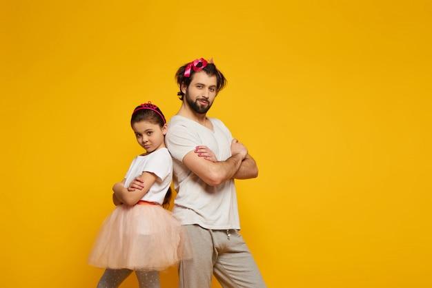 Pai e filha que levantam com os braços akimbo.