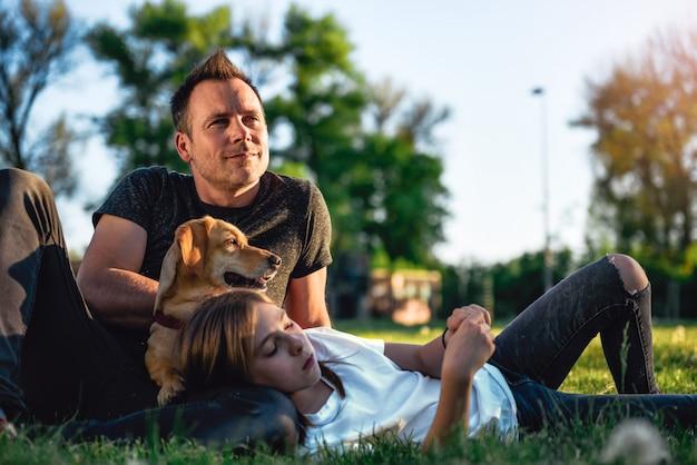 Pai e filha relaxante no parque com cachorro