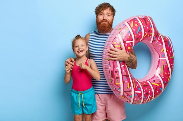 Pai e filha ruivos posando em trajes de piscina