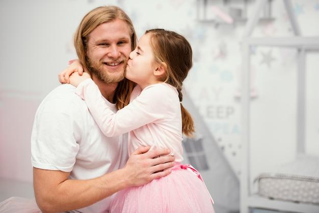 Pai e filha se abraçando em casa com espaço de cópia