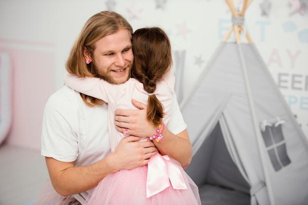 Pai e filha se abraçando em casa